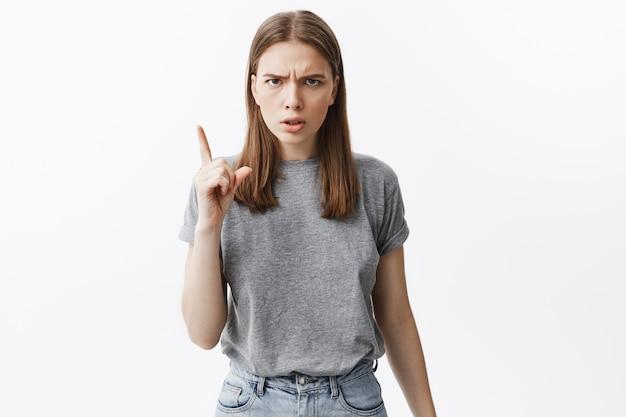 Nie rób już tego. portret pięknej ciemnowłosej nieszczęśliwej dziewczyny w szarych przypadkowych ubraniach gestykuluje ręką, z wyrazem gniewnej twarzy.