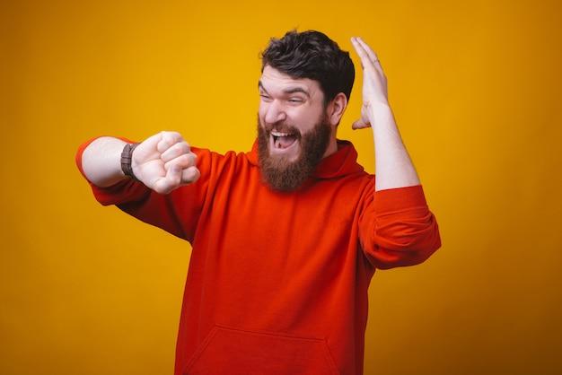 Nie spóźnij się. zdjęcie brodatego mężczyzny patrzy nerwowo na zegarek na rękę trzymający dłoń na głowie.