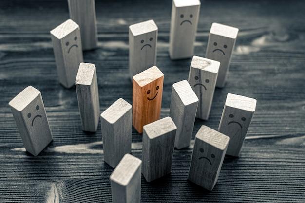 Nie tak jak inne, koncepcja indywidualności i wyjątkowości - kolorowa uśmiechnięta postać między smutnymi postaciami