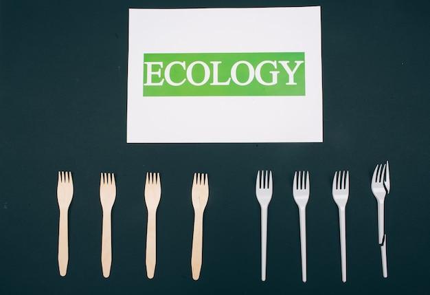 Nie używaj plastiku. zero marnowania. papier z napisem ekologia w pobliżu ekologicznych, naturalnych i jednorazowych widelców w rzędzie na ciemnej powierzchni, widok z góry. plastikowy produkt jednorazowego użytku lub produkt wielokrotnego użytku do recyklingu. zmniejszyć
