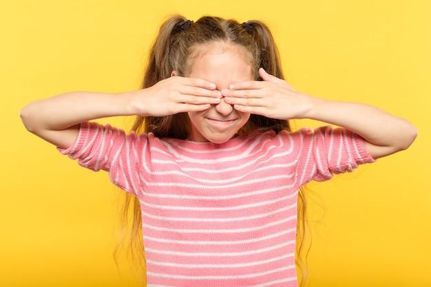 Nie widzę zła. słodkie uśmiechnięte dziewczyny obejmujące oczy rękami. portret na żółto.