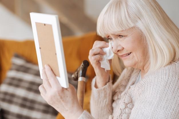 Nie wiem, jak teraz żyć. nieszczęśliwa, przygnębiona starsza kobieta trzymająca papierową chusteczkę i płacząca na widok zdjęcia męża