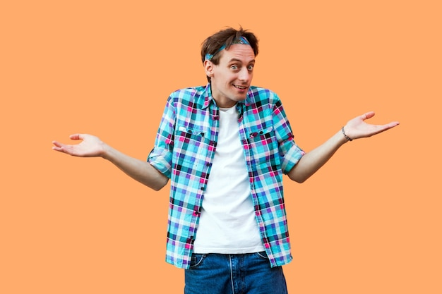 Nie wiem portret zdezorientowany młody człowiek w dorywczo niebieską koszulę w kratkę pałąk stojący podniesionymi rękami i patrząc na kamery z wątpliwą twarzą. kryty strzał studio, na białym tle na pomarańczowym tle.