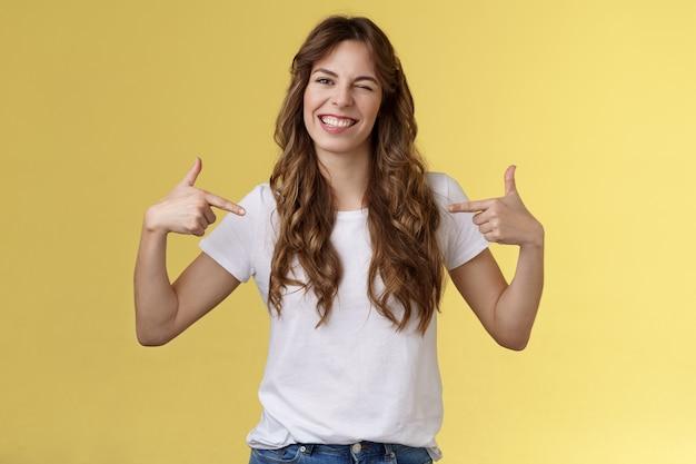 Nie żałujesz tego. sassy przystojny wychodzący odważny młoda kobieta wskazując centrum kopii przestrzeni wskazującej siebie mrugając radośnie pokazuje idealną kandydaturę stoisko żółte tło