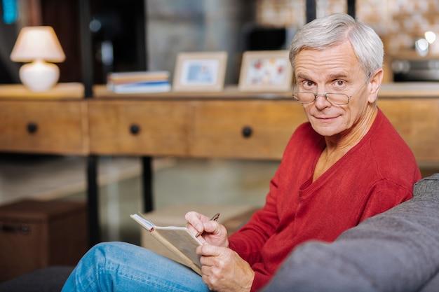 Nie zapomnieć. inteligentny miły starszy mężczyzna trzyma swój notatnik i robi notatki, siedząc na kanapie
