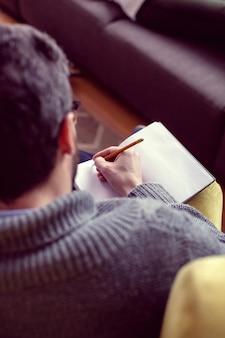 Nie zapomnieć. widok z góry ładny przystojny mężczyzna, robienie notatek siedząc na krześle