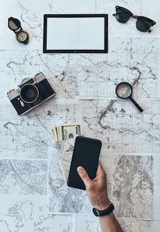 Nie zapomnij! bliska widok z góry mężczyzny trzymającego inteligentny telefon, paszport i pieniądze w okularach przeciwsłonecznych