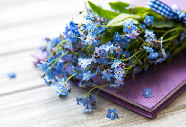 Nie zapomnij o kwiatach i notatniku na białym drewnianym tle