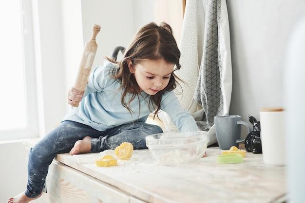 Nie zostawiaj dzieci samych w domu, mogą zrobić coś do jedzenia. zdjęcie całkiem małej dziewczynki, która siedzi na stole w kuchni i bawi się mąką.