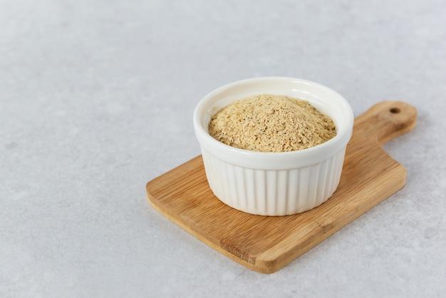 Nieaktywne drożdże w białej misce na drewnianej desce