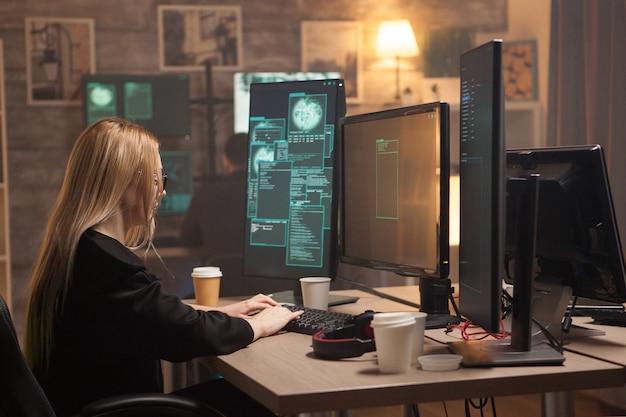 Niebezpieczna kobieta haker pisze wirusa na komputerze, aby ukraść tożsamość karty kredytowej.