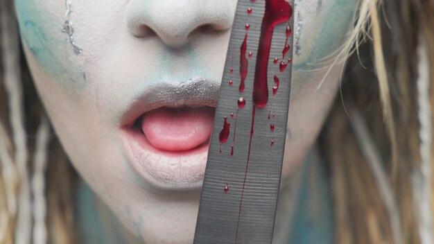 Niebezpieczna kobieta liże nóż z bliska krwi. motyw halloween lub horror