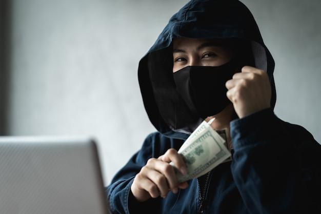 Niebezpieczna kobieta z kapturem hakerka trzymała pieniądze po udanym hakowaniu.