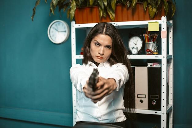 Niebezpieczna kobieta z pistoletem w biurze. szalony lub szalony zły młody bizneswoman mające na celu prosto w kamerę. koncepcja kryzysu. przyciemniony obraz