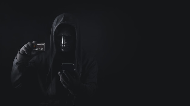 Niebezpieczny anonimowy haker w zakapturzonym użyciu smartfona, trzymając kartę kredytową