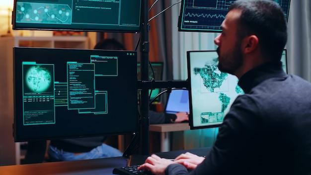 Niebezpieczny haker oglądający wiele monitorów podczas pracy. cyberprzestępca.