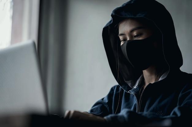 Niebezpieczny haker z kapturem, który używa komputera, włamuje się do danych