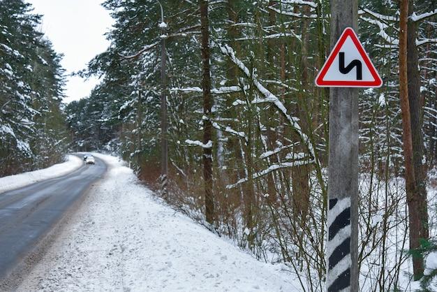 Niebezpieczny odcinek zaśnieżonej drogi zimą, znak drogowy.