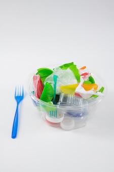 Niebezpieczny plastik. przezroczysty przezroczysty pojemnik wypełniony śmieciami i śmieciami z przygotowanym widelcem w pobliżu