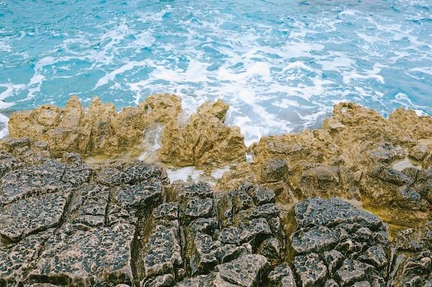 Niebezpieczny skalisty brzeg morza z widokiem z góry drona lazurowej wody