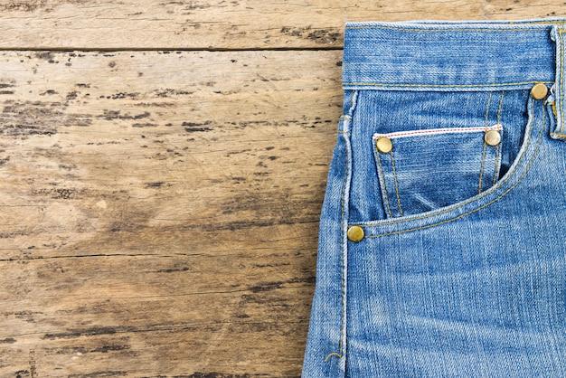 Niebiescy dżinsy na brown drewnianym tle. zamyka up niebiescy dżinsy