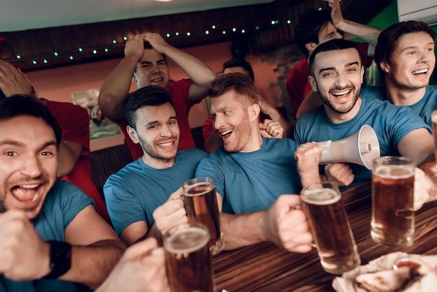 Niebiescy fani drużyny świętują i kibicują w barze.