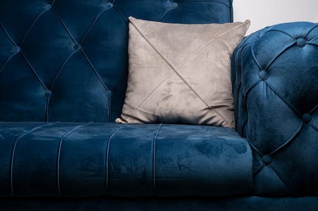 Niebieska aksamitna sofa z szarą poduszką