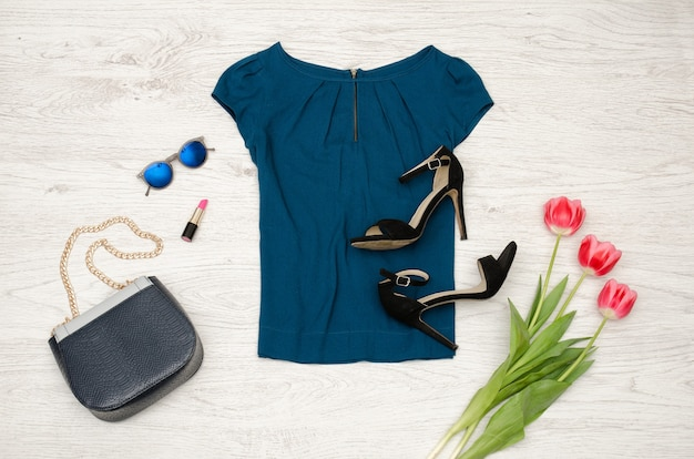 Niebieska bluzka, torebka, okrągłe okulary, szminka, czarne buty i różowe tulipany