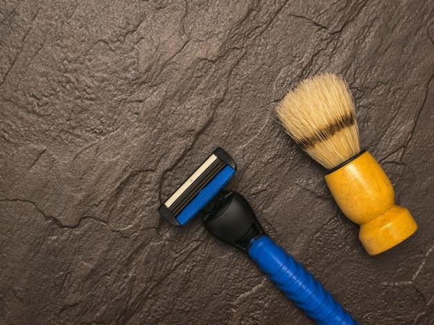 Niebieska brzytwa i pędzel do golenia dla mężczyzn na kamiennym stole. zestaw do pielęgnacji męskiej twarzy. leżał na płasko.