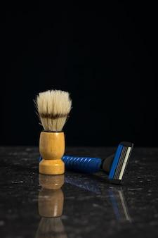 Niebieska brzytwa męska i pędzel do golenia z drewnianą rączką na kamiennym tle. zestaw do pielęgnacji męskiej twarzy.