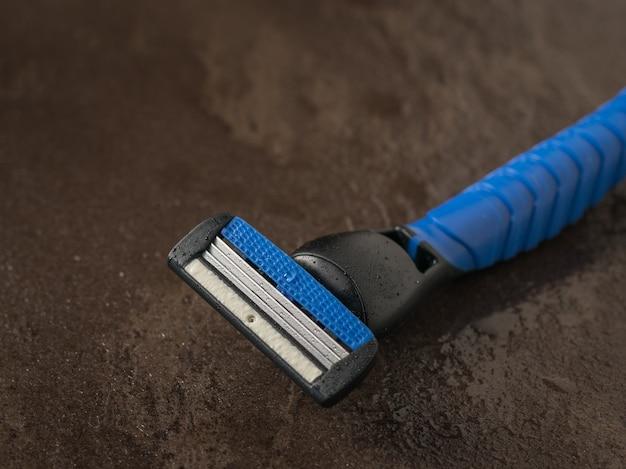 Niebieska brzytwa męska na mokrej powierzchni kamienia. zestaw do pielęgnacji męskiej twarzy. leżał płasko.