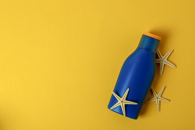Niebieska butelka kremu przeciwsłonecznego i rozgwiazdy na żółto