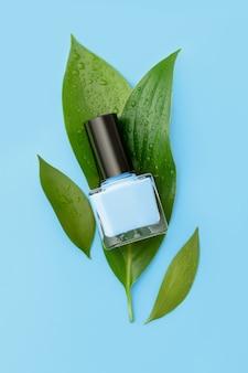 Niebieska butelka lakieru do paznokci na białej powierzchni.