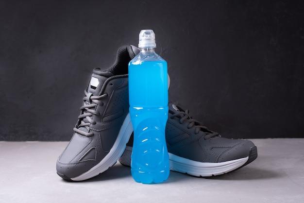 Niebieska butelka napoju izotonicznego do odzyskania równowagi wodno-solnej po treningu na czarnym tle, z bliska.