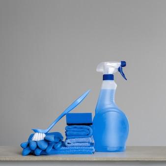 Niebieska butelka z rozpylaczem do czyszczenia z plastikowym dozownikiem, gąbką, szczotką do szorowania naczyń, ściereczką do kurzu i gumowymi rękawiczkami na szaro