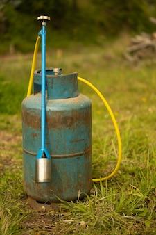 Niebieska butla z gazem i palnik na trawie