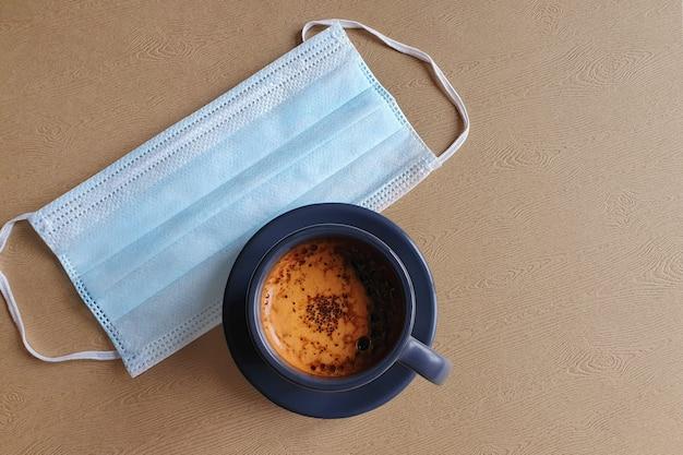 Niebieska chirurgiczna maska ochronna i filiżanka kawy na drewnianym stole. widok z góry