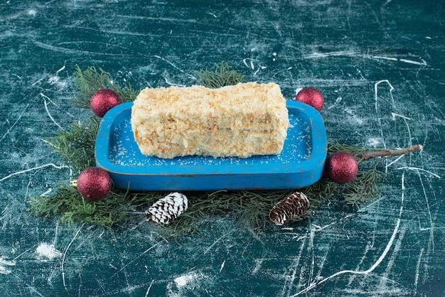 Niebieska deska ze słodkim tortem bułkowym i bożonarodzeniowymi szyszkami. zdjęcie wysokiej jakości