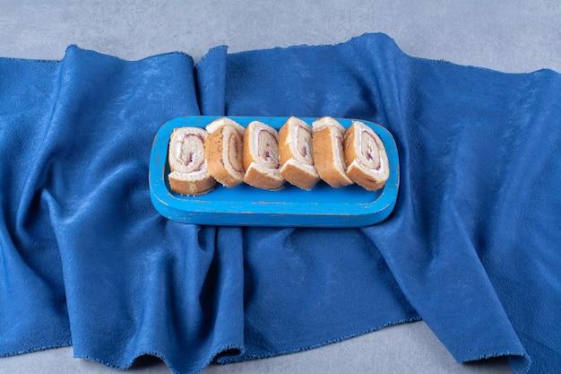 Niebieska deska ze słodkimi pokrojonymi w plastry bułeczkami na obrusie.