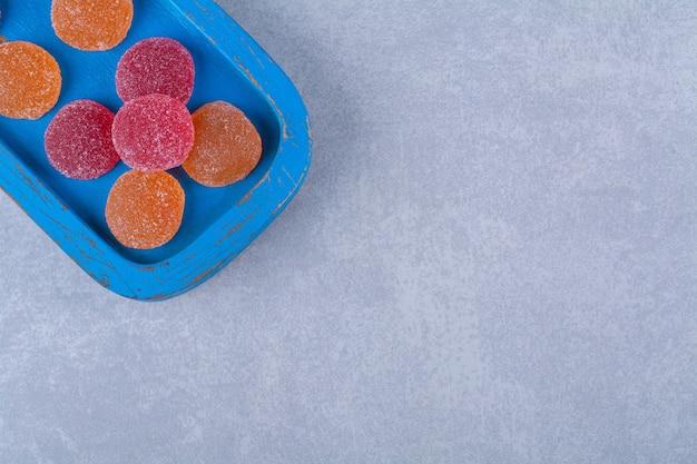 Niebieska drewniana deska pełna czerwonych i pomarańczowych słodkich marmolad