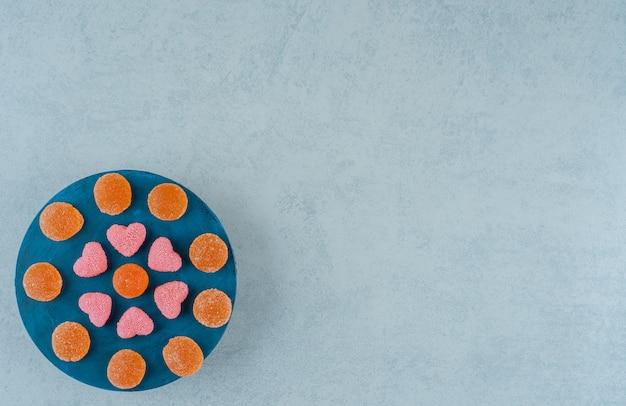 Niebieska drewniana deska pełna pomarańczowych cukierków z galaretką z galaretką w kształcie serca