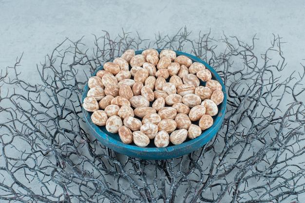 Niebieska drewniana deska pełna słodkich pysznych pierników na białej powierzchni