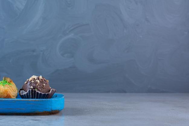 Niebieska drewniana deska z dwoma czekoladowymi babeczkami i baklawą.