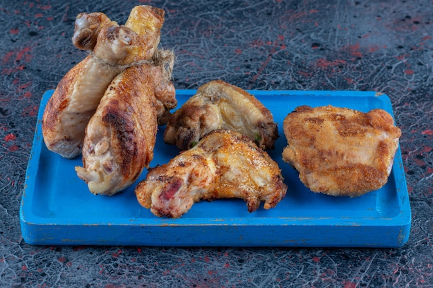 Niebieska drewniana deska z grillowanego mięsa z kurczaka.
