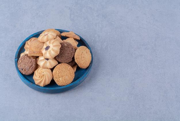 Niebieska drewniana deska ze słodkimi okrągłymi pysznymi ciasteczkami na worze.