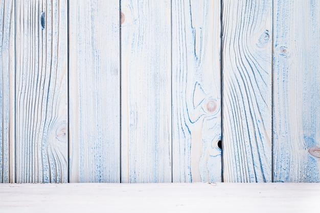 Niebieska drewniana ściana, pomalowana w stylu shabby chic i biała podłoga