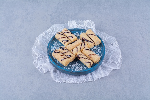 Niebieska drewniana tablica słodkich paluszków z posypką i syropem czekoladowym.