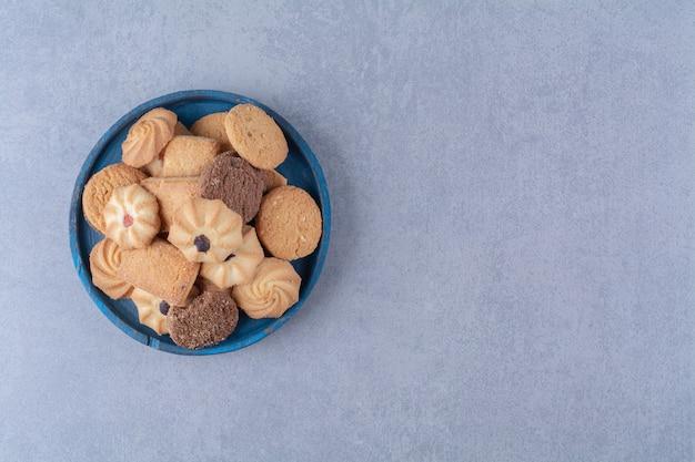 Niebieska drewniana tablica ze słodkimi okrągłymi pysznymi ciasteczkami na worze.