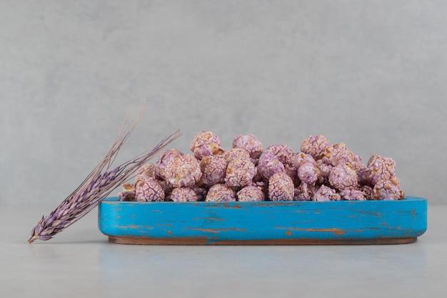 Niebieska drewniana taca wypełniona popcornowymi cukierkami i fioletową łodygą pszenicy na marmurowym tle.