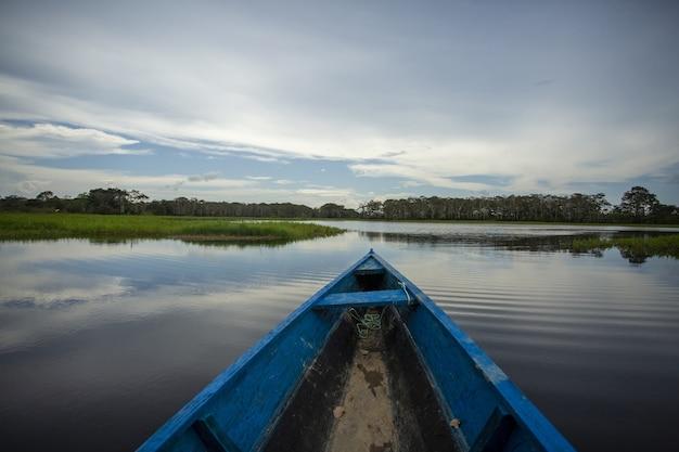 Niebieska drewniana zardzewiała łódź w jeziorze otoczona pięknymi zielonymi drzewami